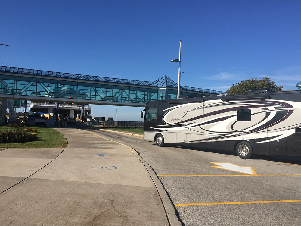 A long motorhome approaches a ferry terminal.