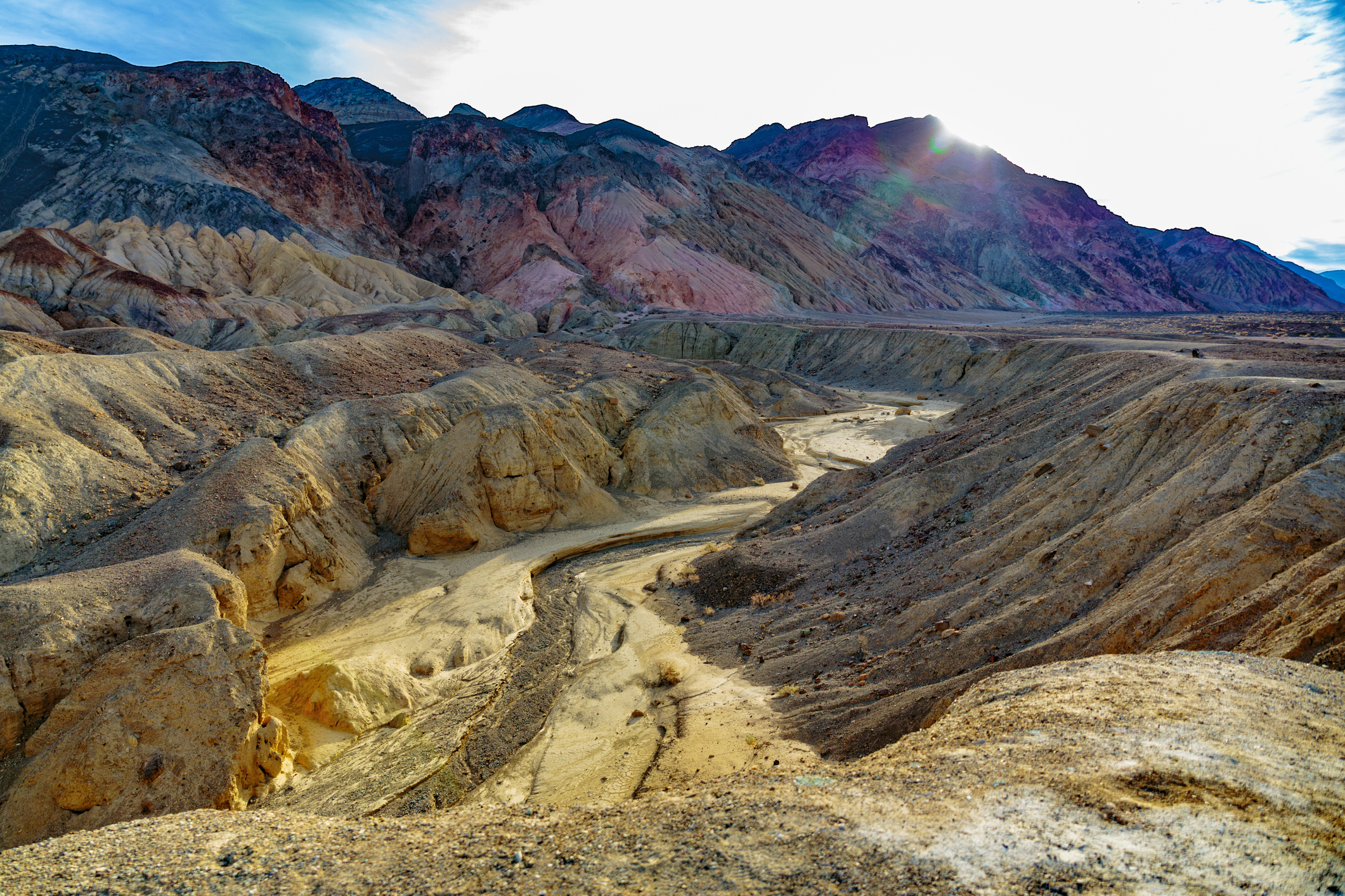 Multi-colored desert hillsides overlooking a wash.