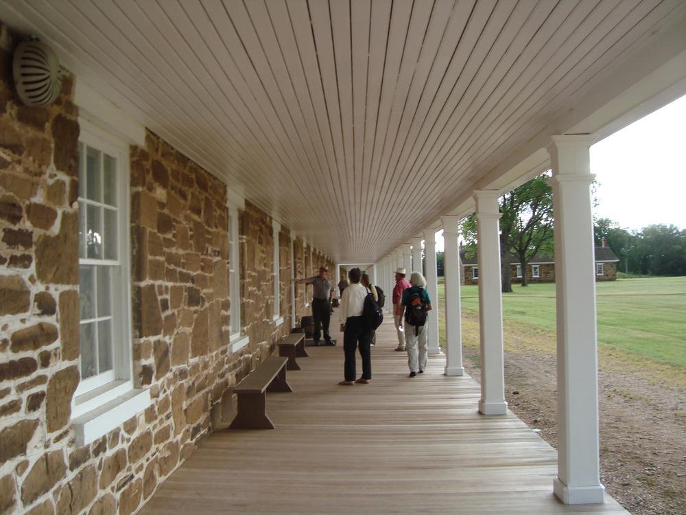 Tourists walk on a wooden sidewalk.