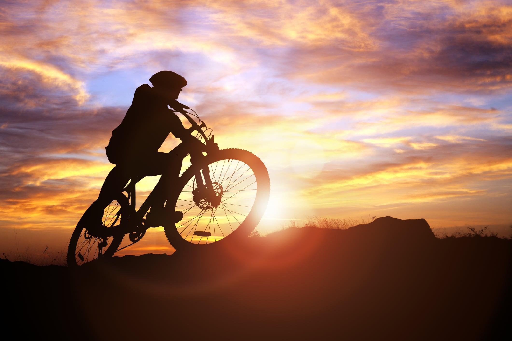 Dude mountain biking at sunset.