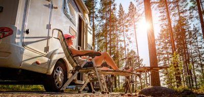 Woman lounging on outdoor chair next to RV in woods