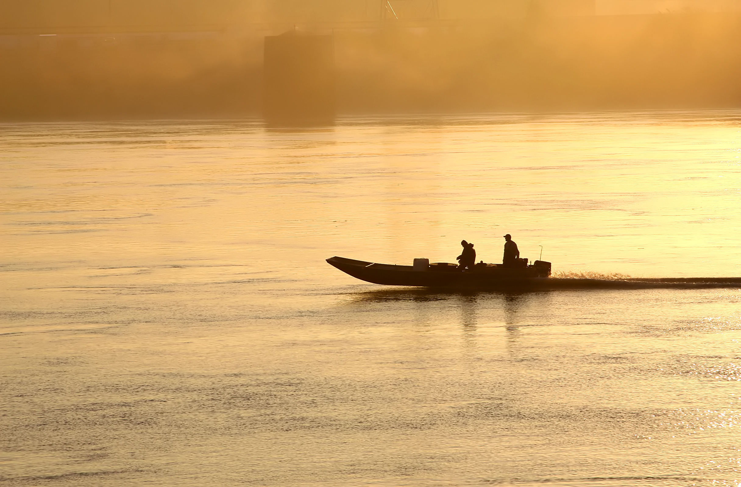 Two people riding skiff at dawn.