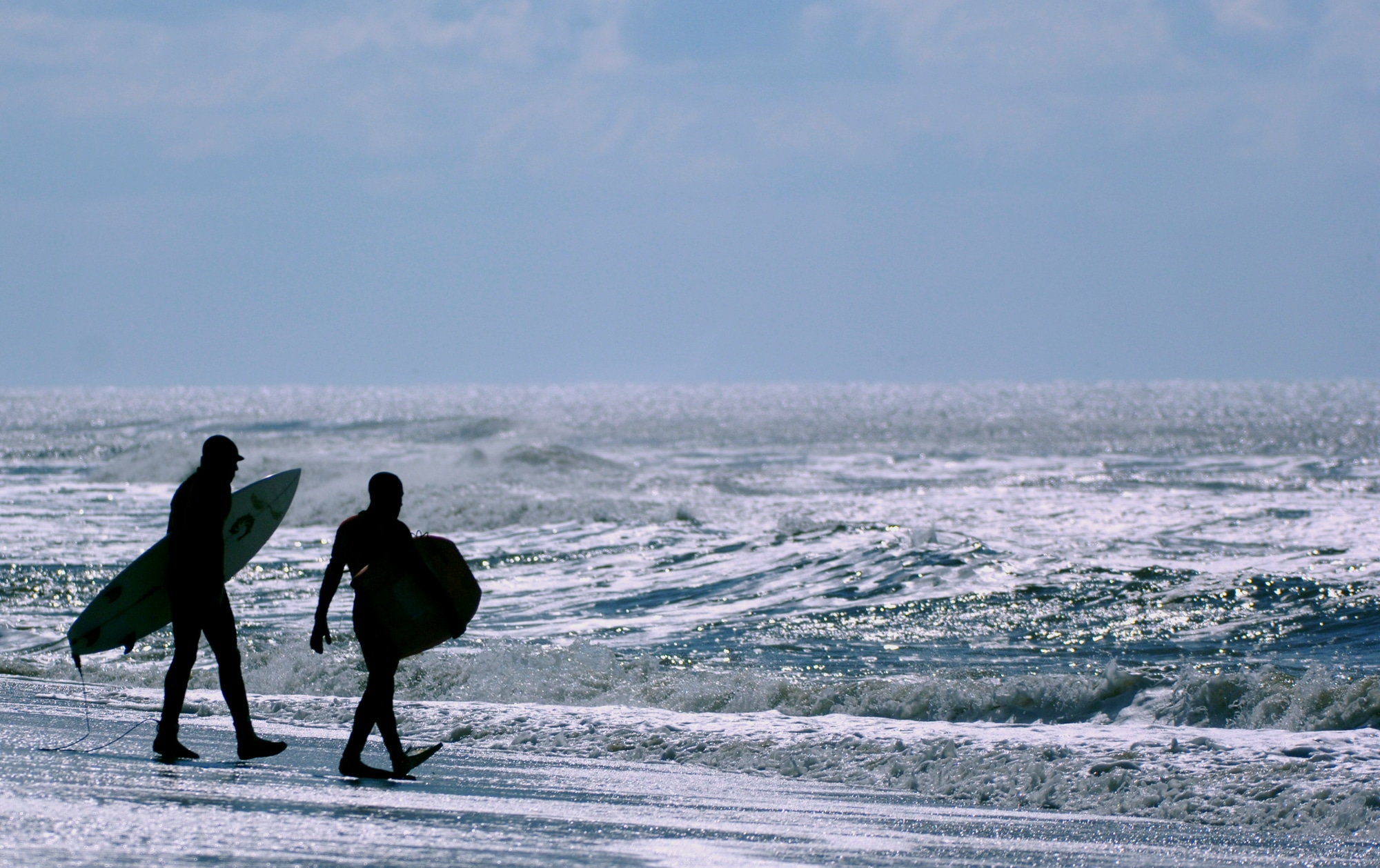 A pair of surfers head toward the waves