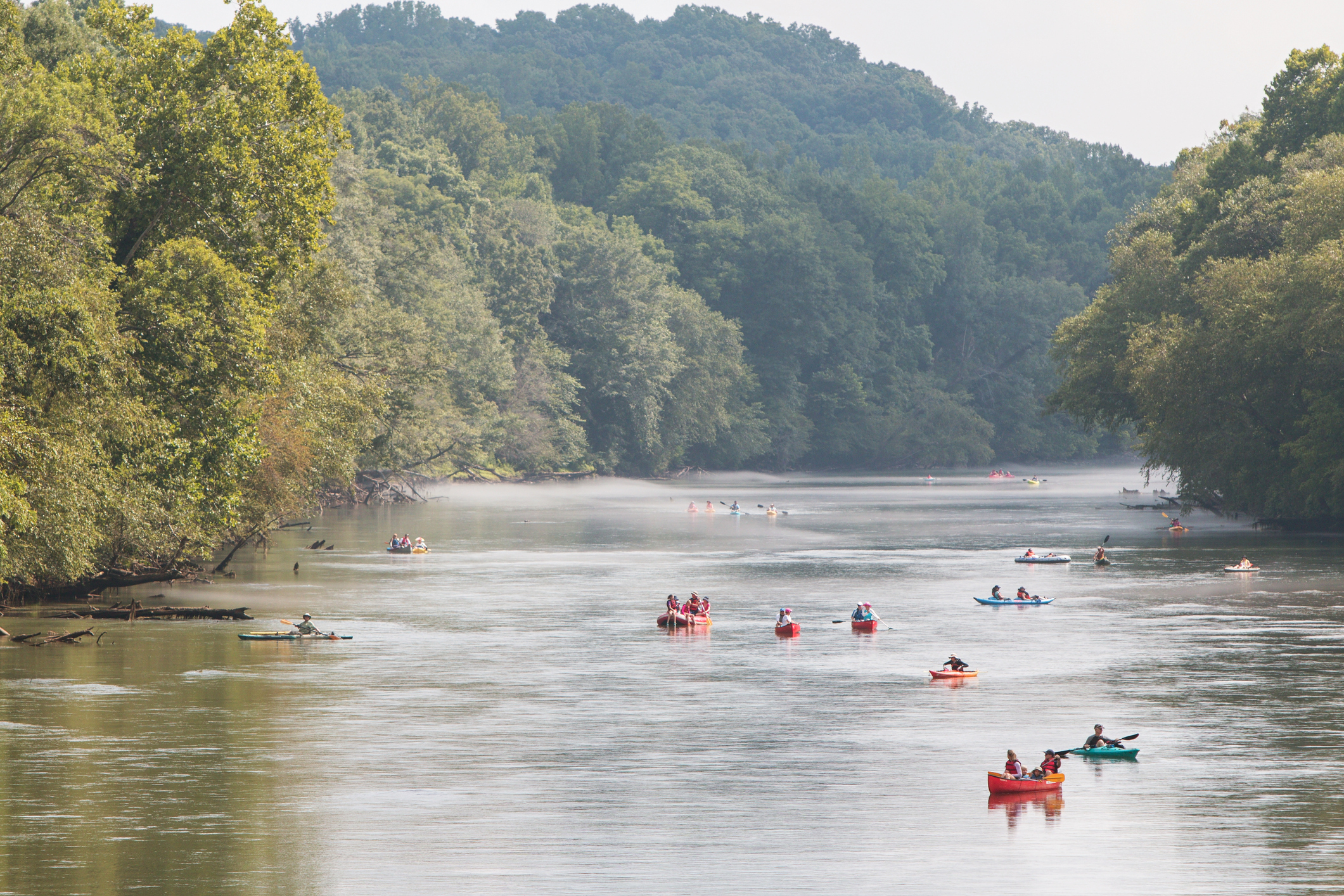 Kayak and rafts on a mellow river.