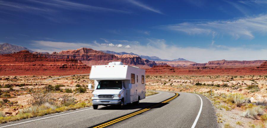 Class C motorhome driving down a desert highway