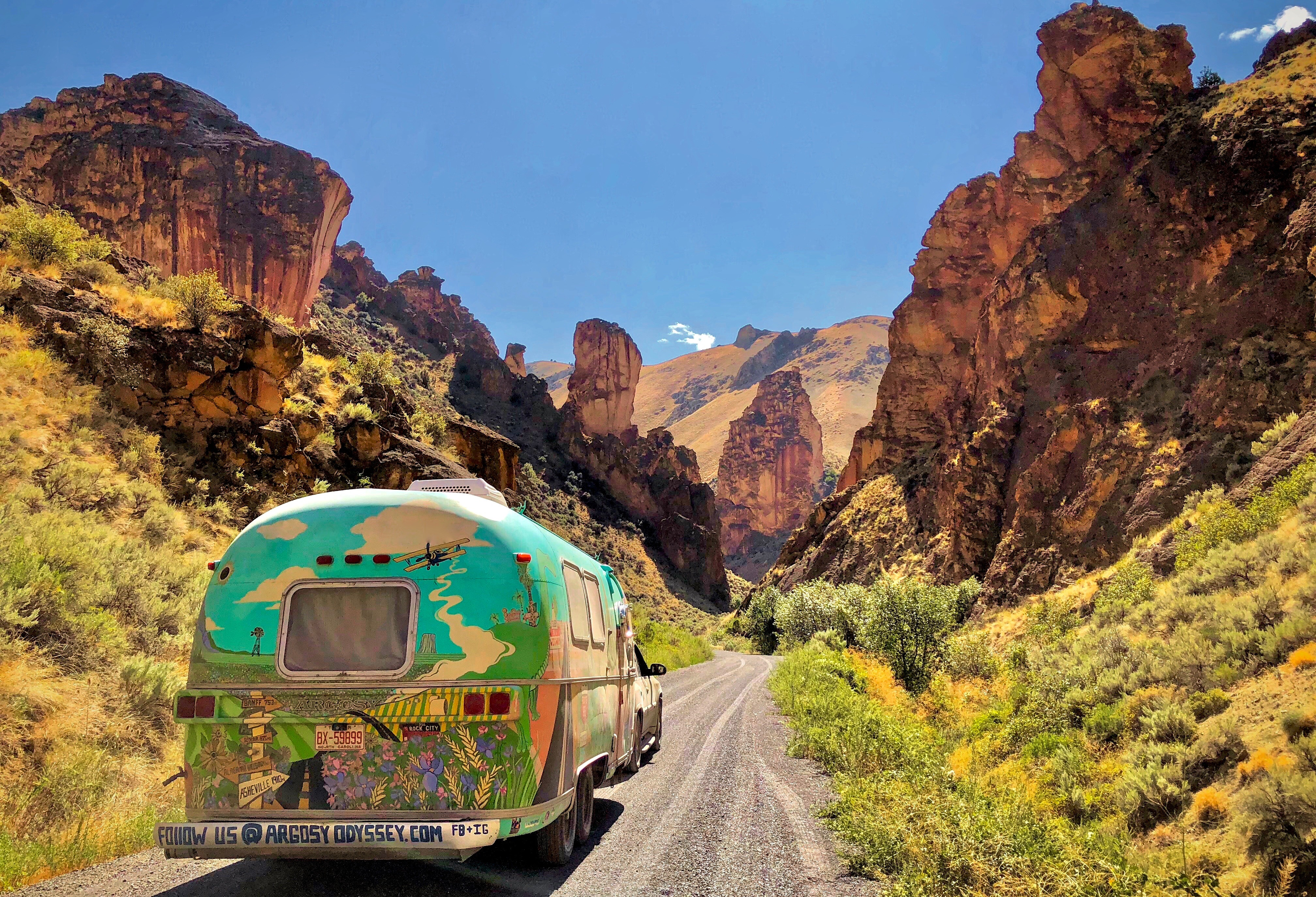 Airstream covered in mural-type paintings on a dirt road