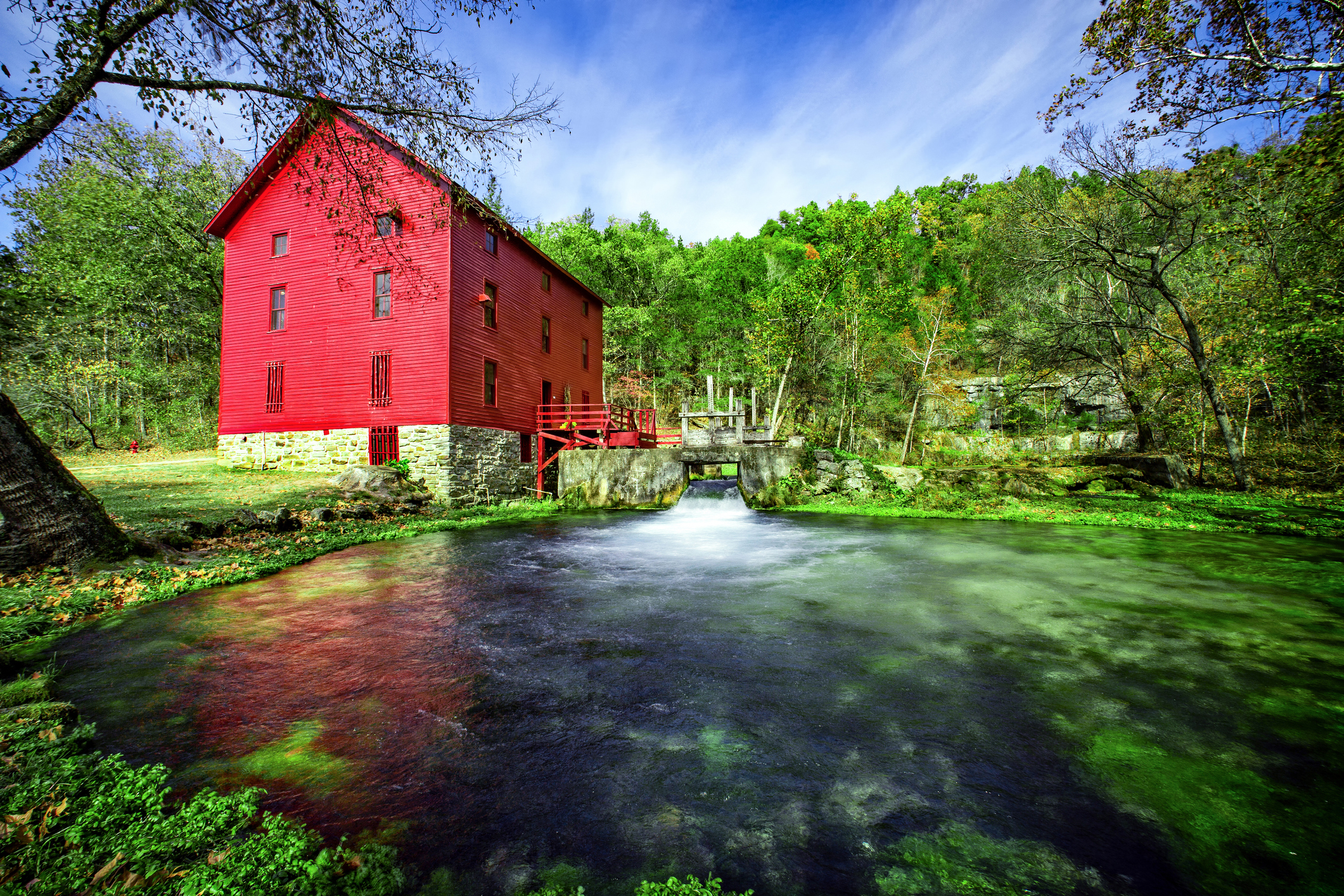 Ozark River running past a large red building.