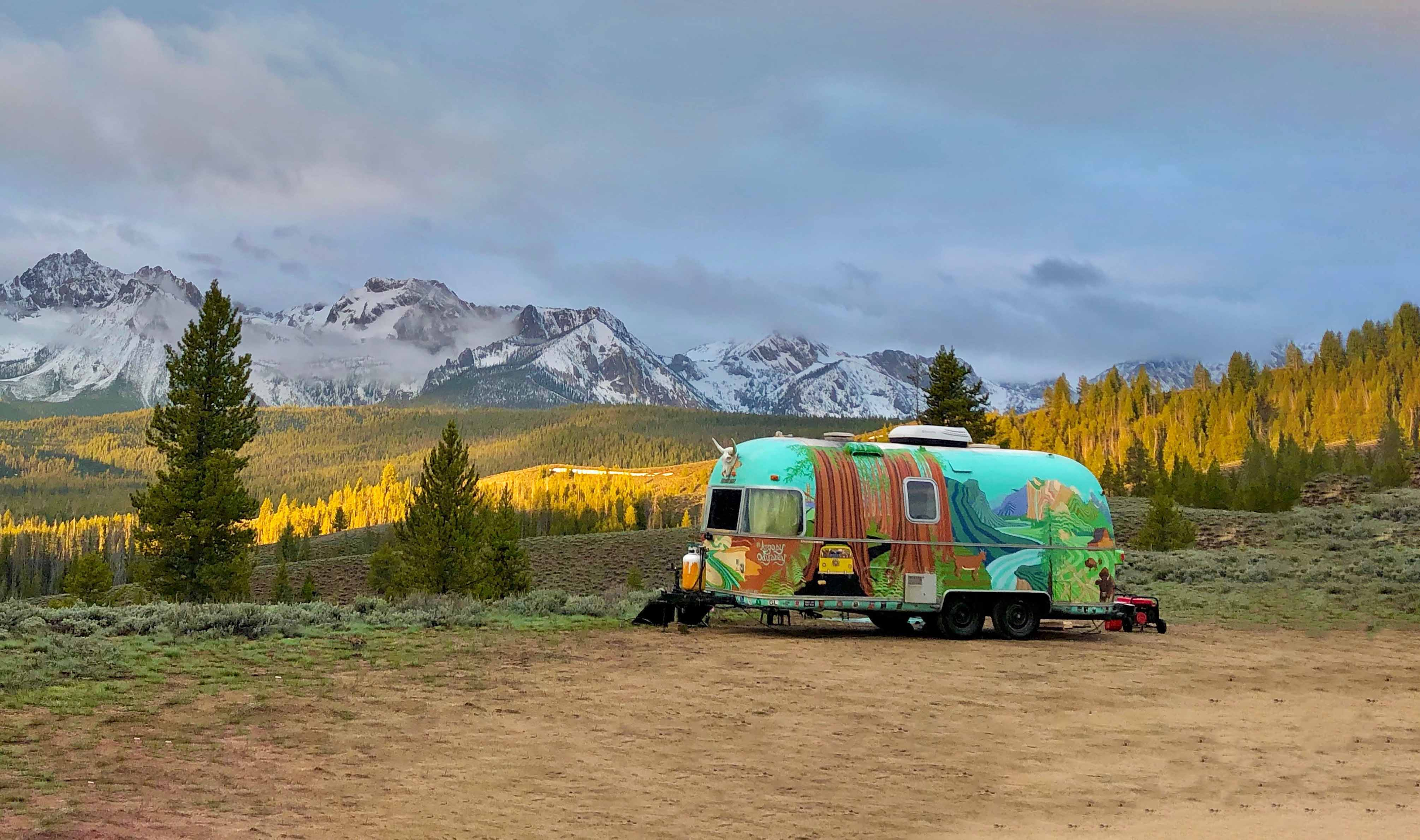 Colorfully painted travel trailer in clearing