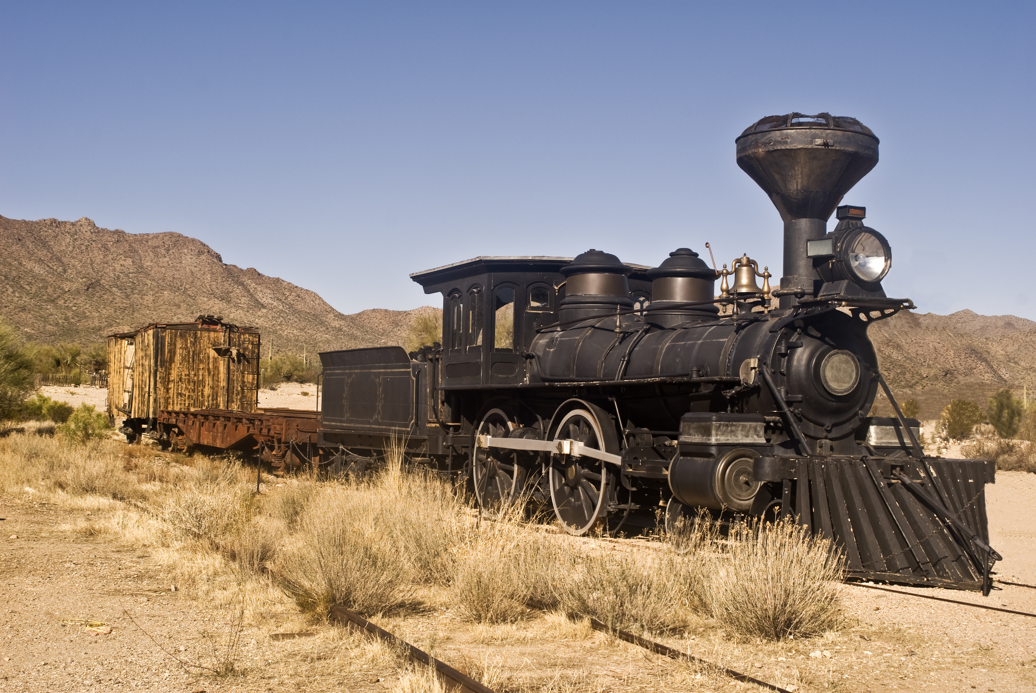 Old steam locomotive in desert setting.