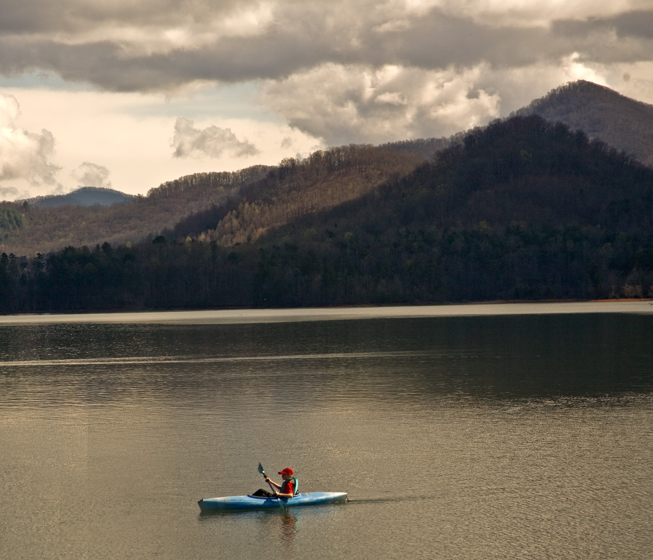A kayaker paddles with forested mountains in the background.
