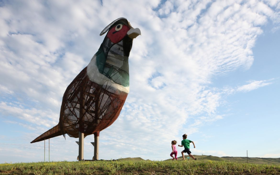 Large bird sculpture on the Enchanted Highway with two kids running nearby