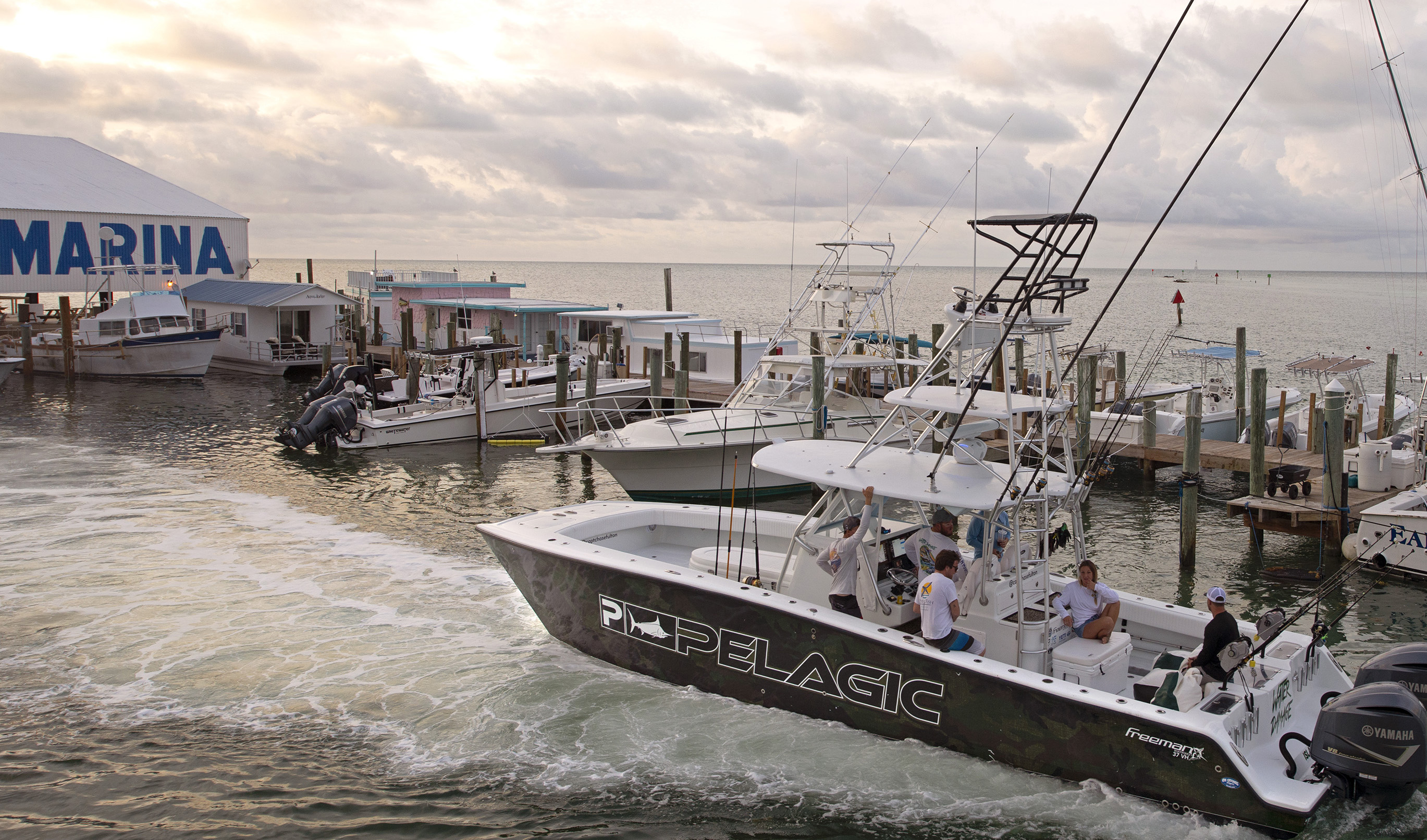 Charter fishing boat departs from marina.