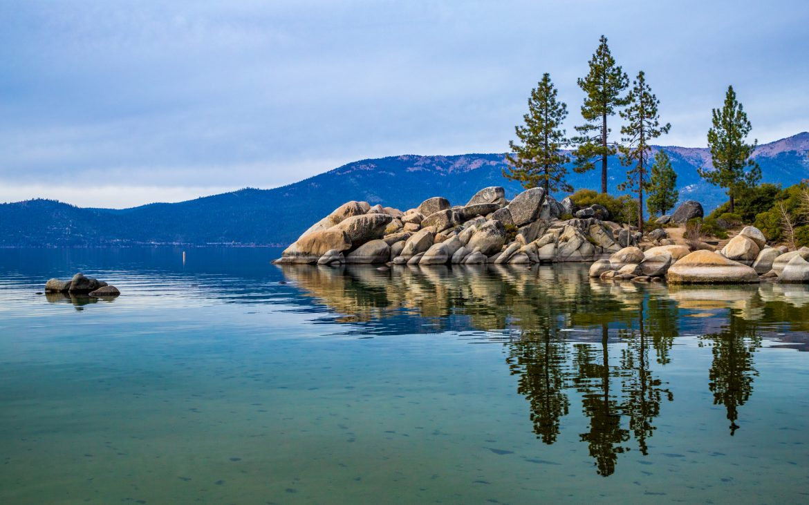 Tall trees atop beautiful boulders and crystal clear water at Sand Harbor with stunning mountains in the background, Lake Tahoe