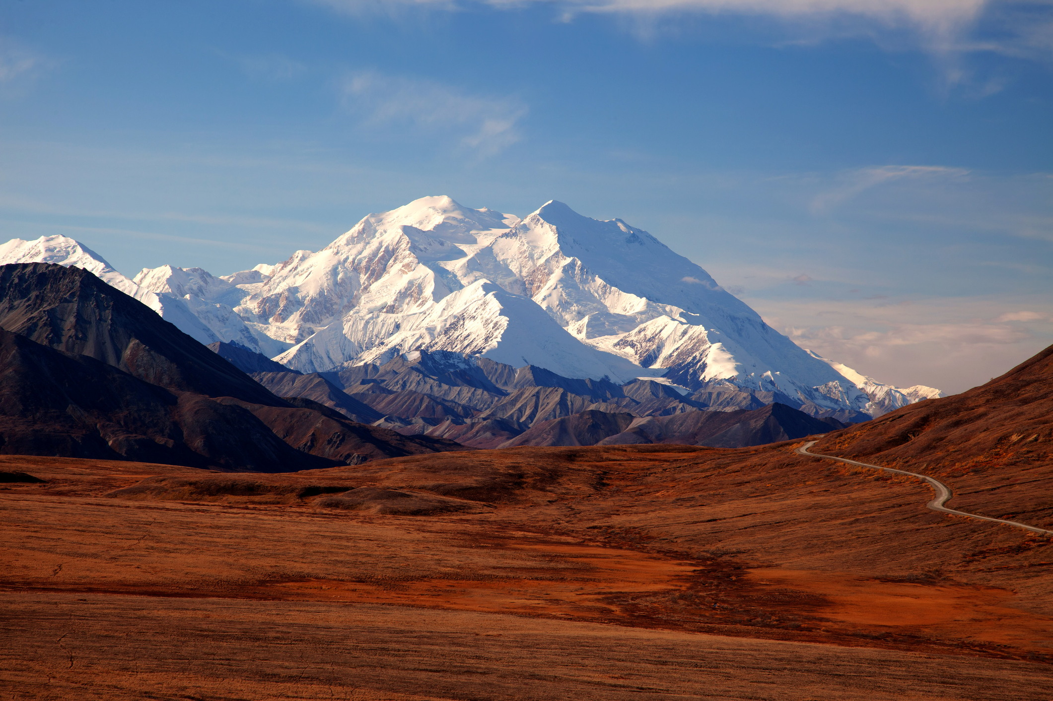 Huge, snow-covered peak rises above the horizon.