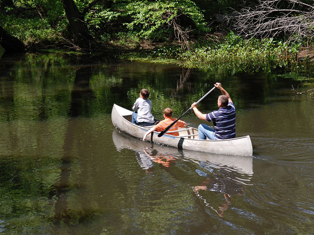 A man paddling a canoe with kids.