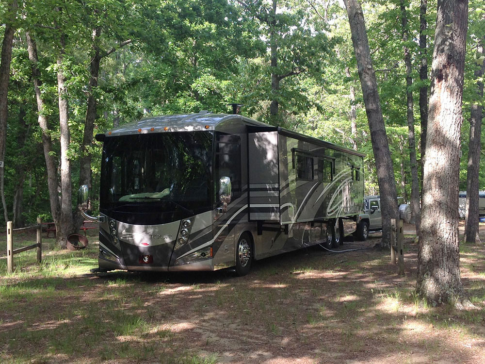 Motorhome with slide-out extended under shade trees.