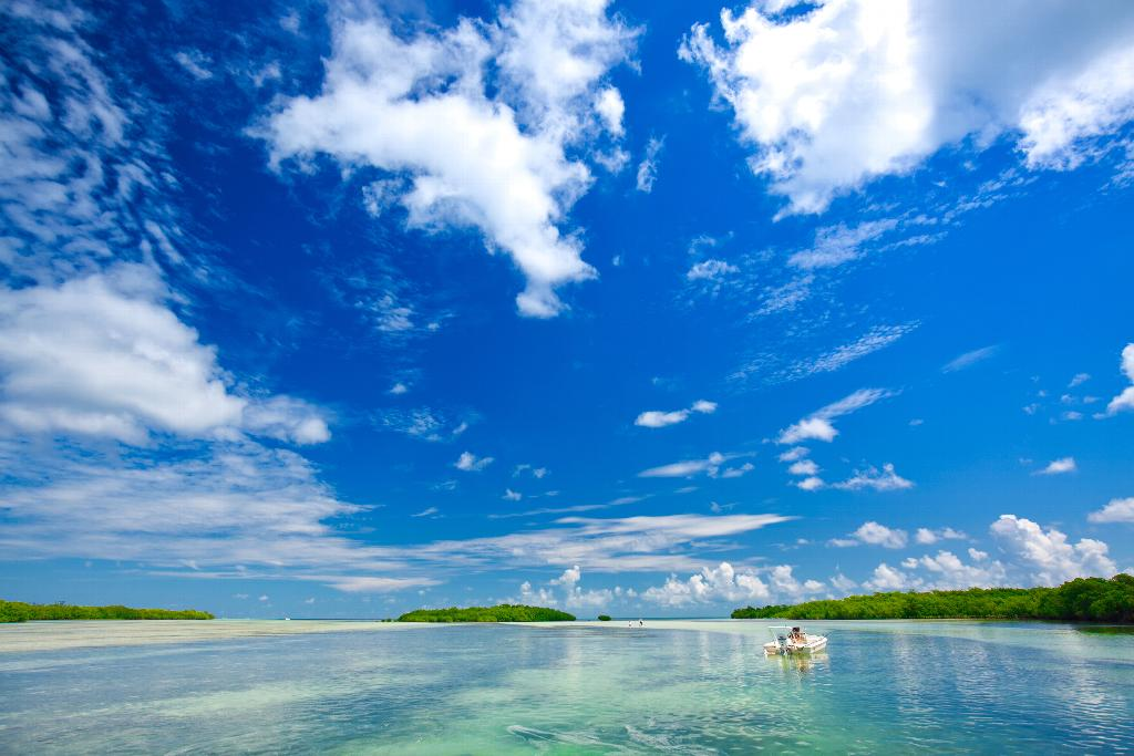 A boat floating on clear waters under a blue sky.
