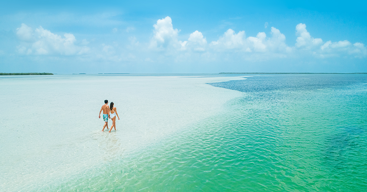 Couple walking on a remote white-sand beach.