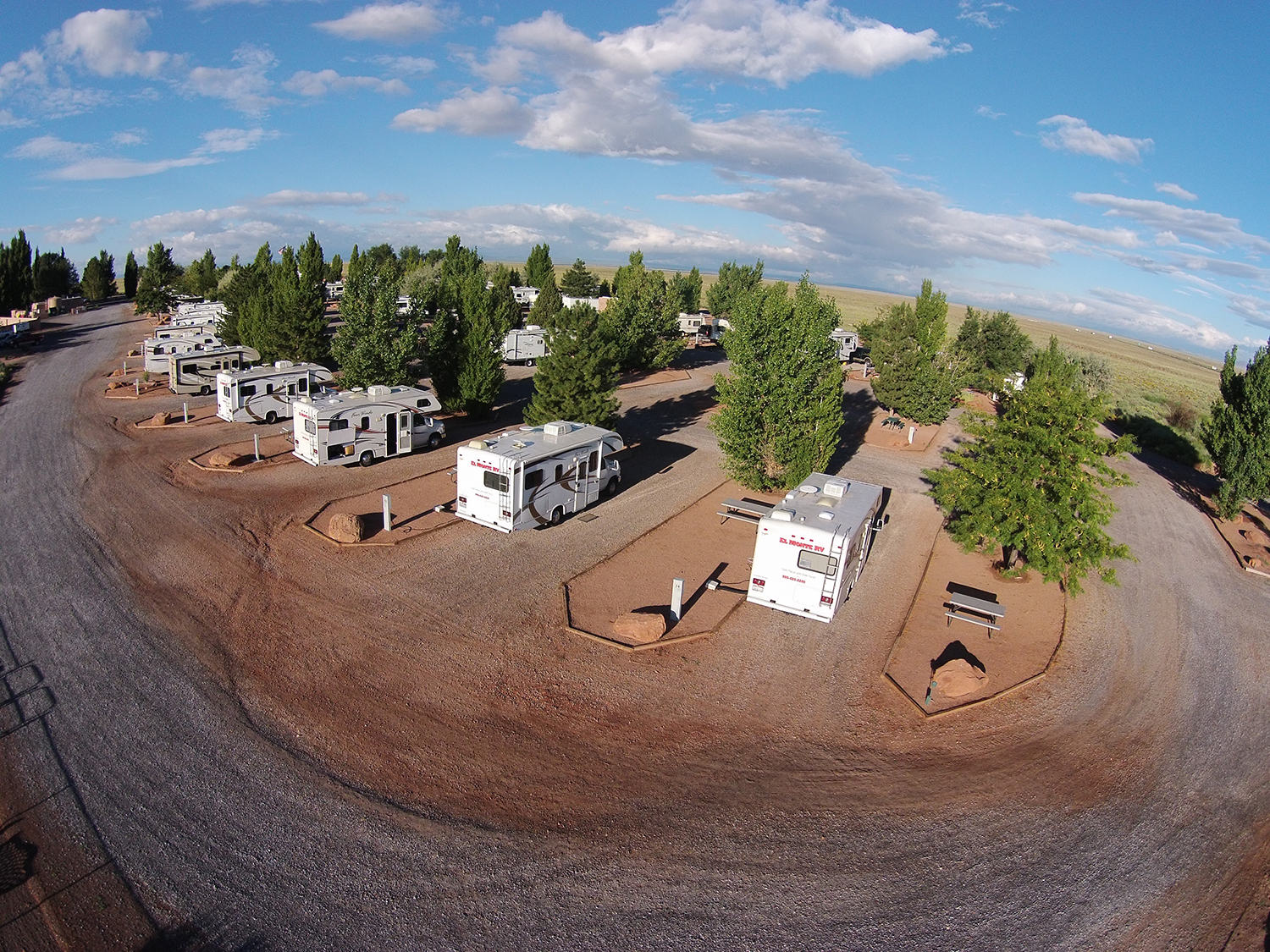 Aerial view of desert RV park with trees.