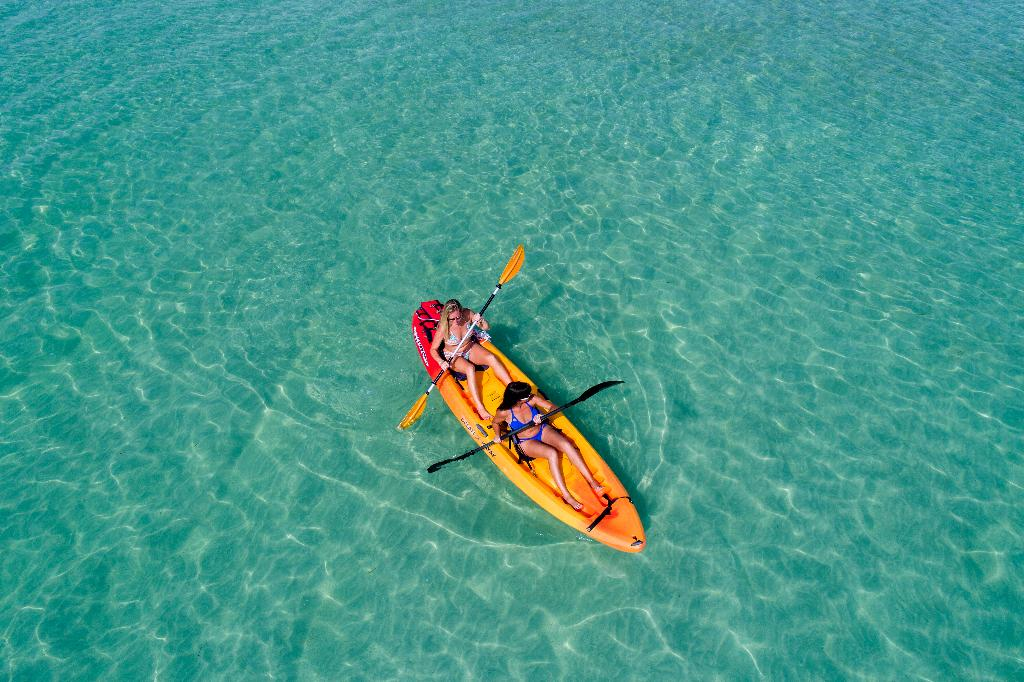 Aerial shot of vkayakers on clear blue water.