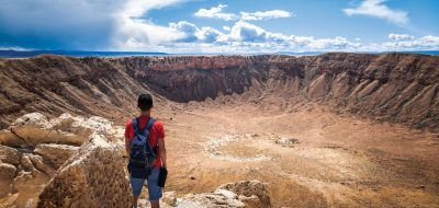 Hiker standing at the edge of large crater.