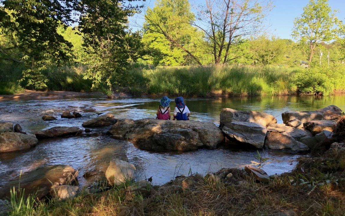 Two kids sitting on rock near creek in Georgia