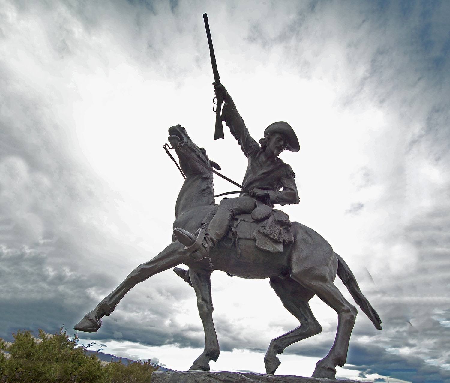 Statue of a cowboy on horseback raising his rifle high