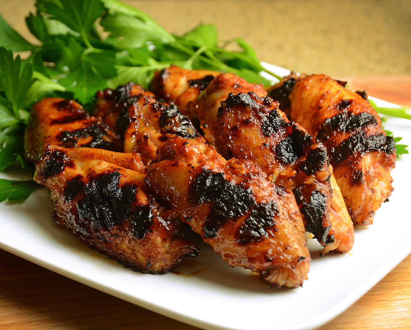Grilled chicken stacked neatly with greens.