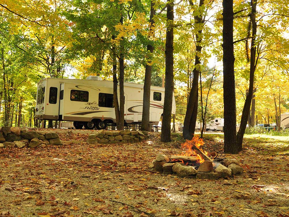 A fifth-wheel trailer parked in an autumn forest.