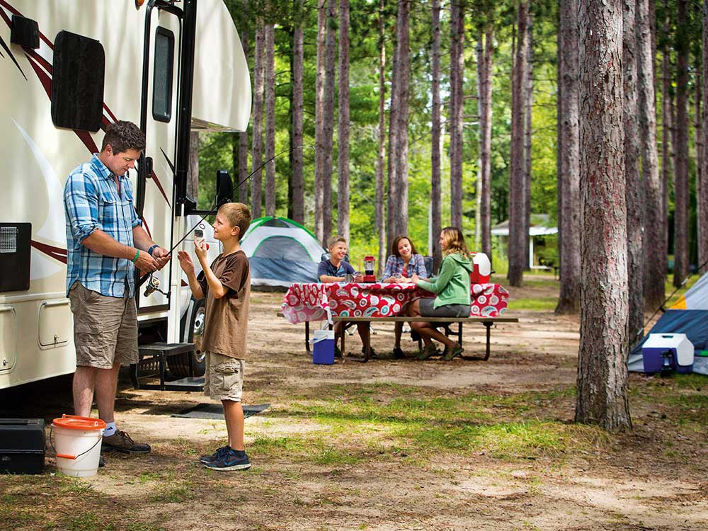 A family camping in thick woods.