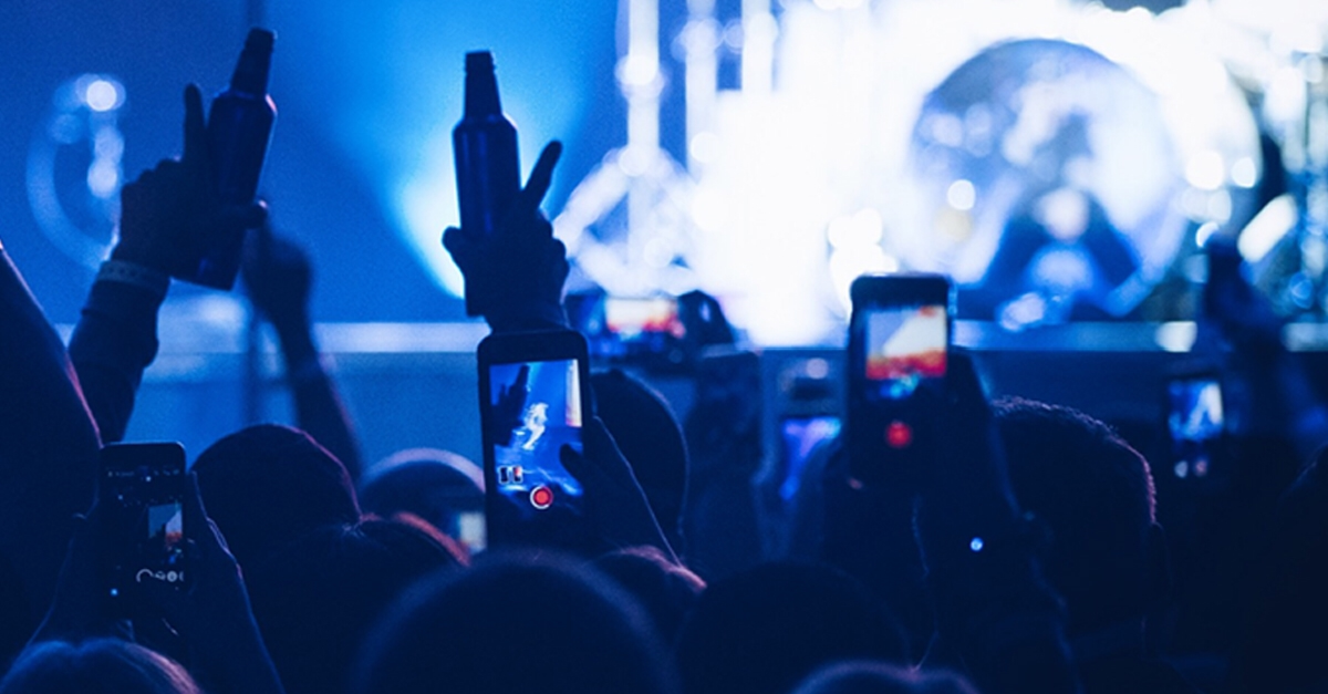 Music fans raise their phones to record a band.