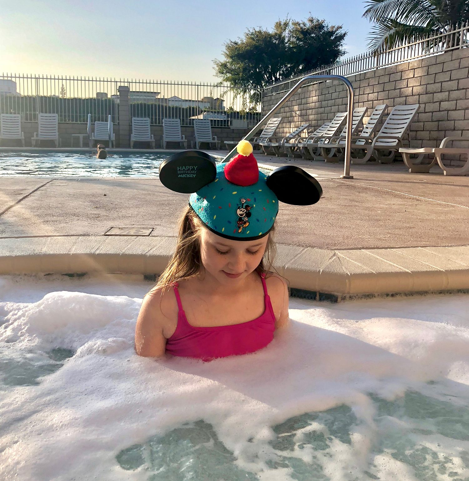Kid in a hot tub with Disney hat.