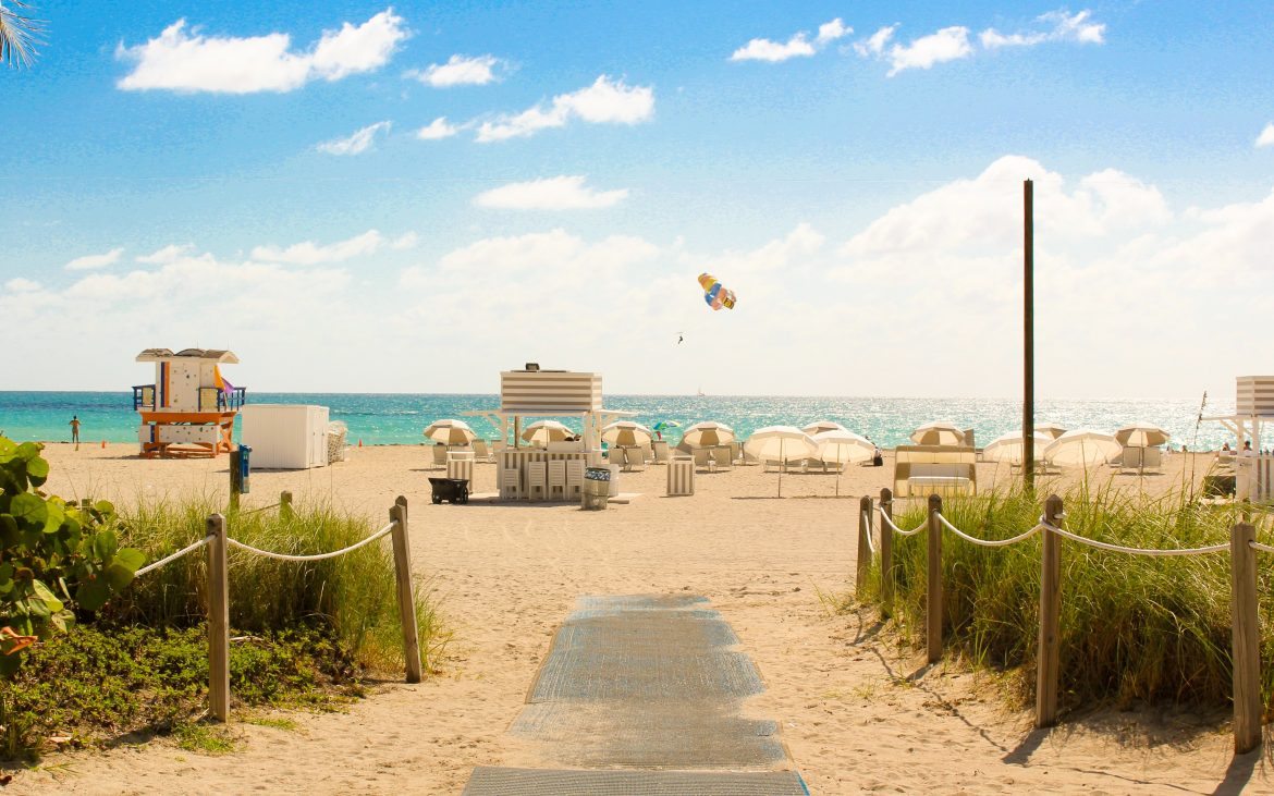 Walkway onto beach with lifeguard tower and chairs at South Beach, Miami Beach