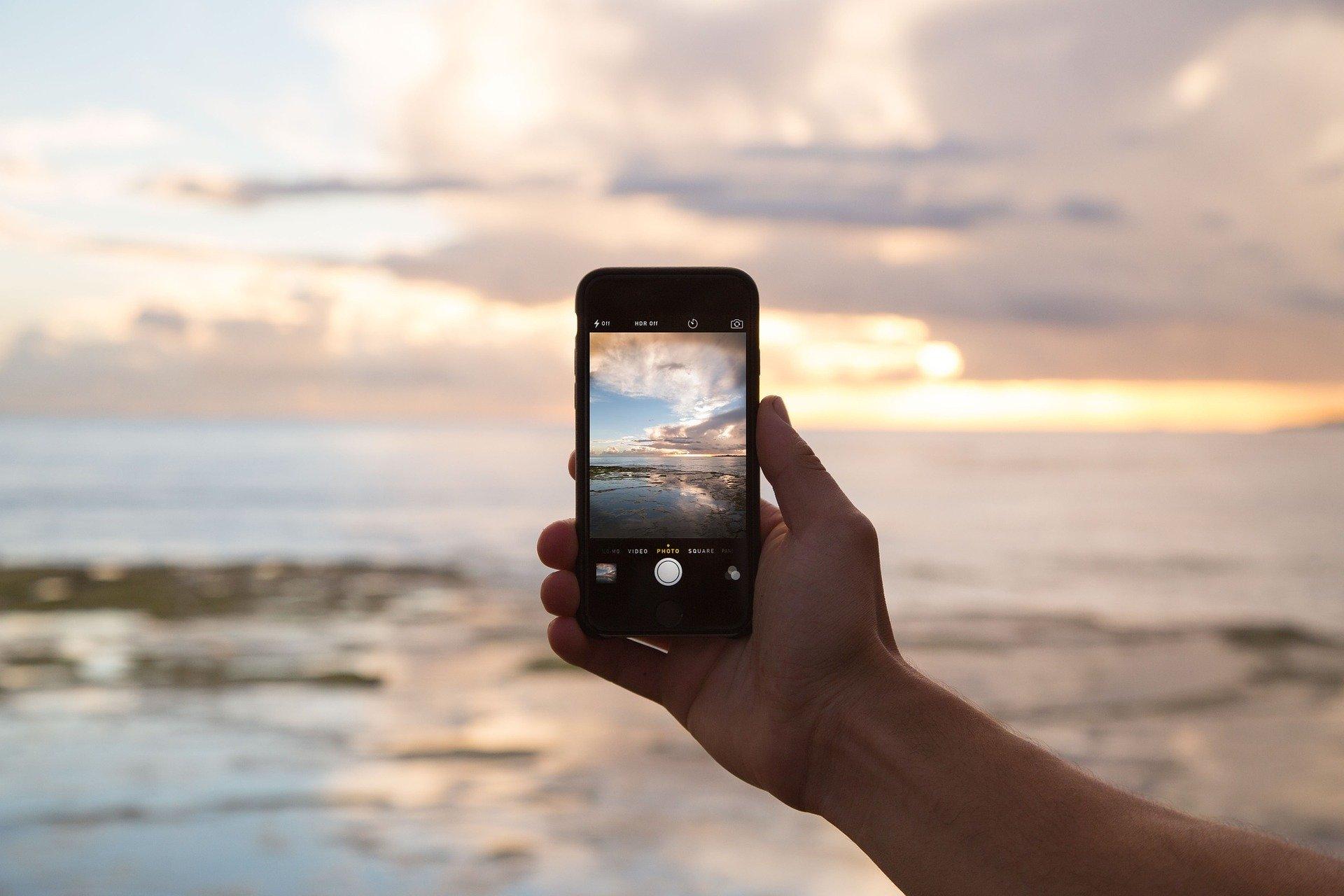Smart phone held up against sky.