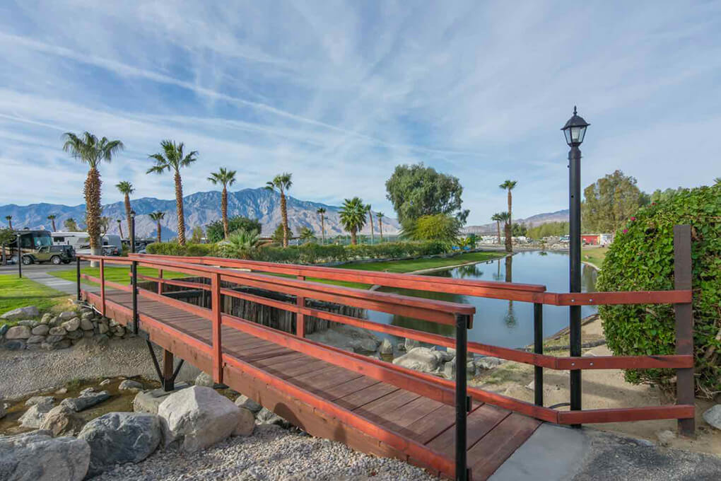 Beautiful pond with wooden bridge surrounded by palm trees at RV Resort in Desert Hot Springs