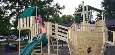 an award-winning campground — Kids play on a boat in a playground.