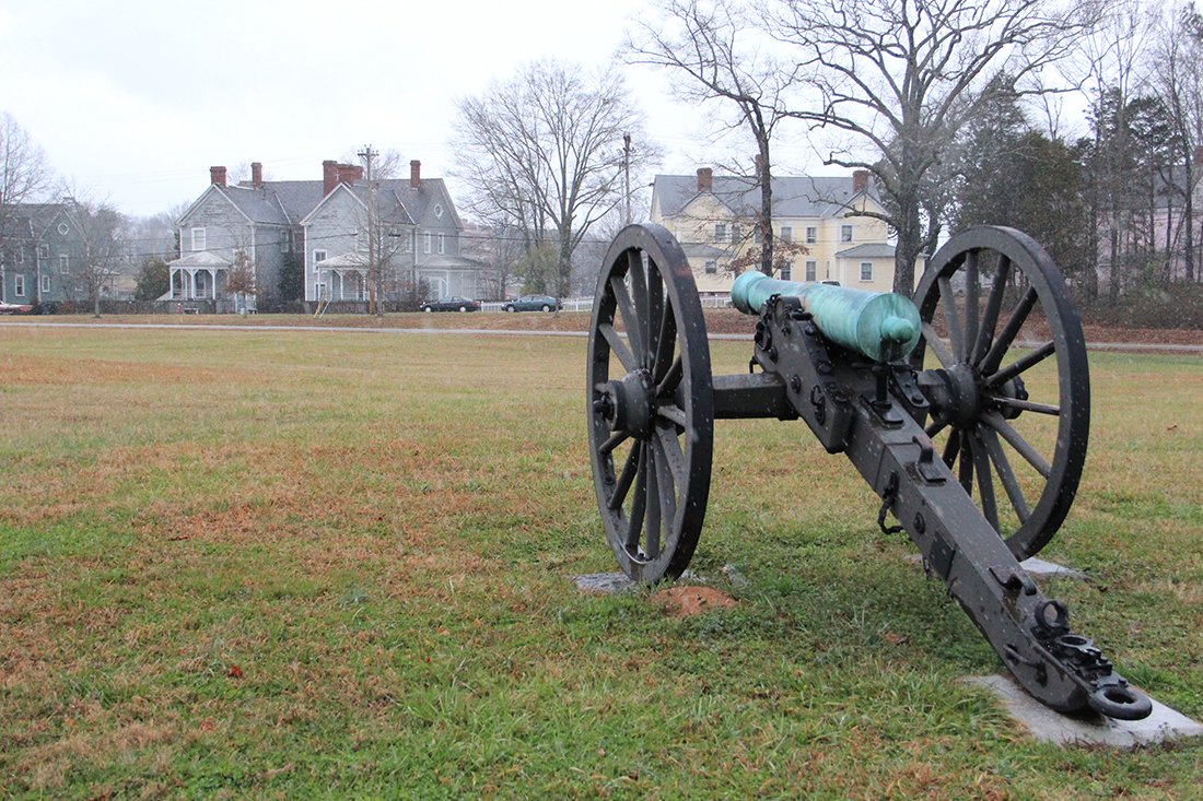 Civil War Cannon pointed at stately buildings.