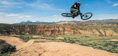 A cyclist gets some air on badlands.