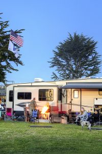RV campers at Pismo Coast Village RV Resort with people in lawn chairs around firepit
