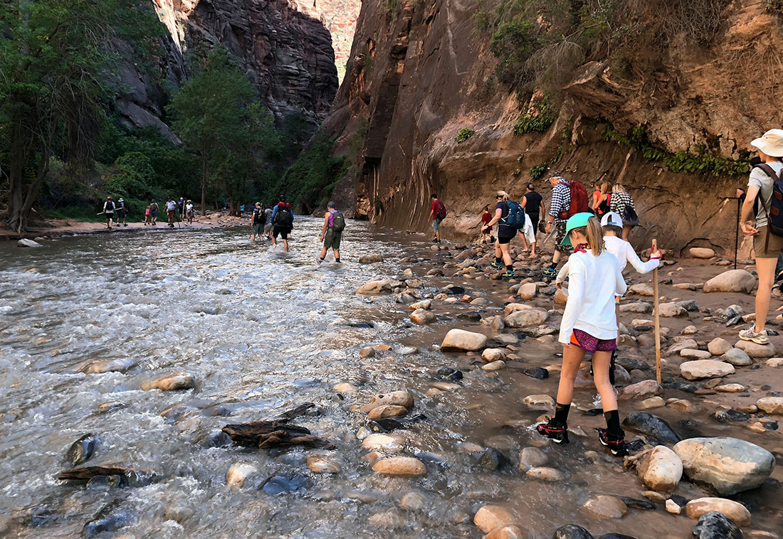 People wade in a shallow river in a chasm