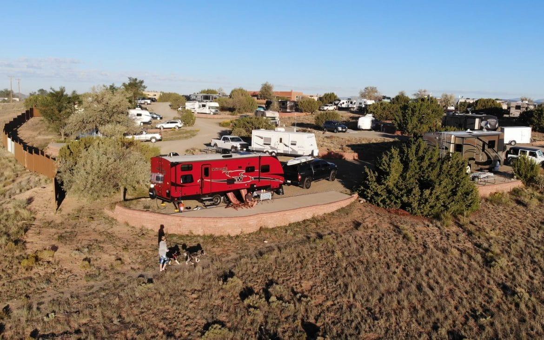 Woman walking dog at Santa Fe Skies RV Park near red Winnebago