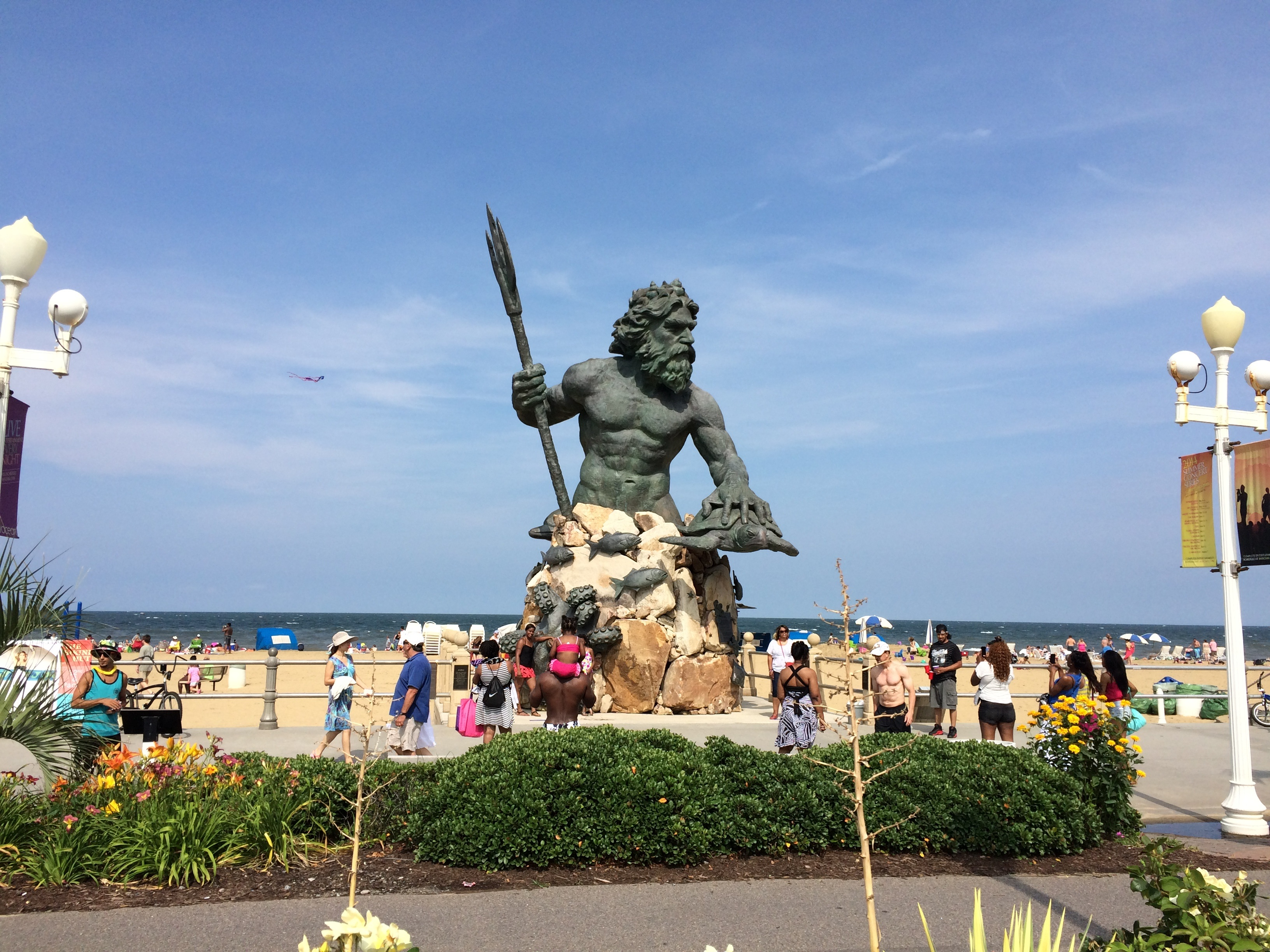 Statue of regal King Neptune with conch at beach area.