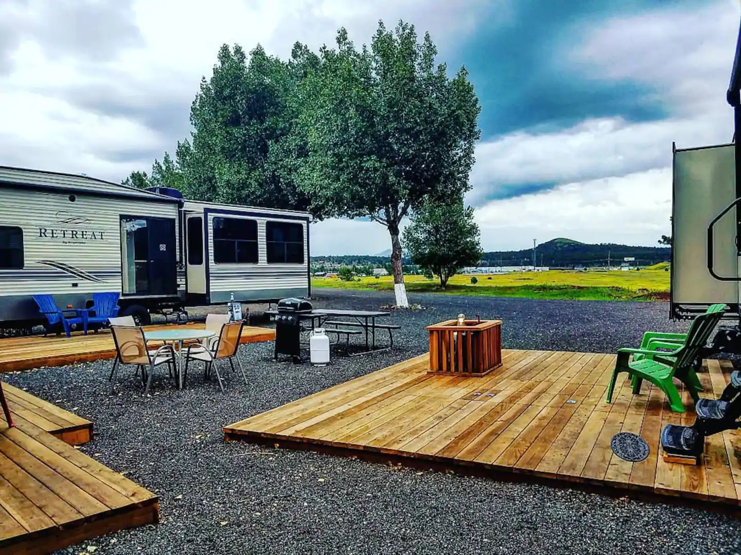 A pair of RV trailers with wooden patios.