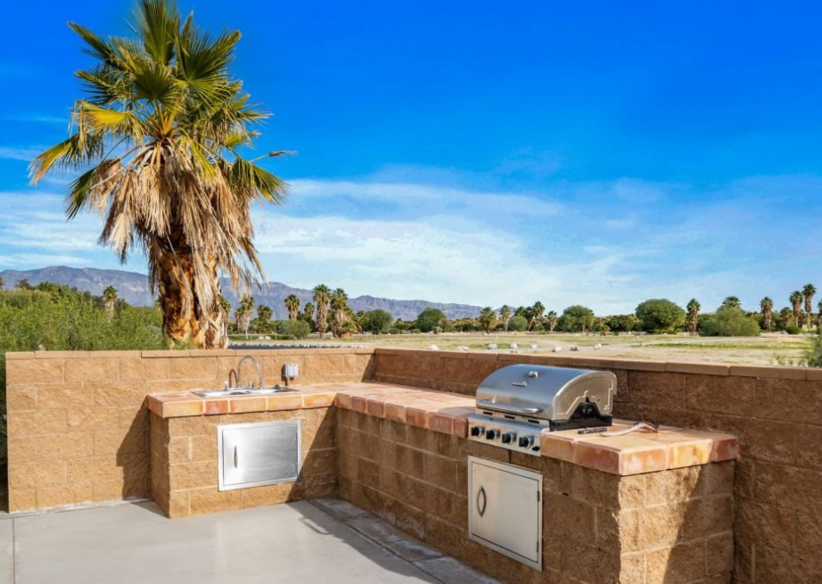 An outdoor grill with view of a palm tree.