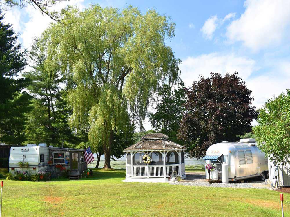 Airstream trailers at a lakeside park near a gazebo.