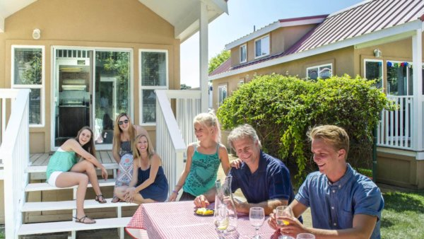 A family dines outside of a beach cottage.