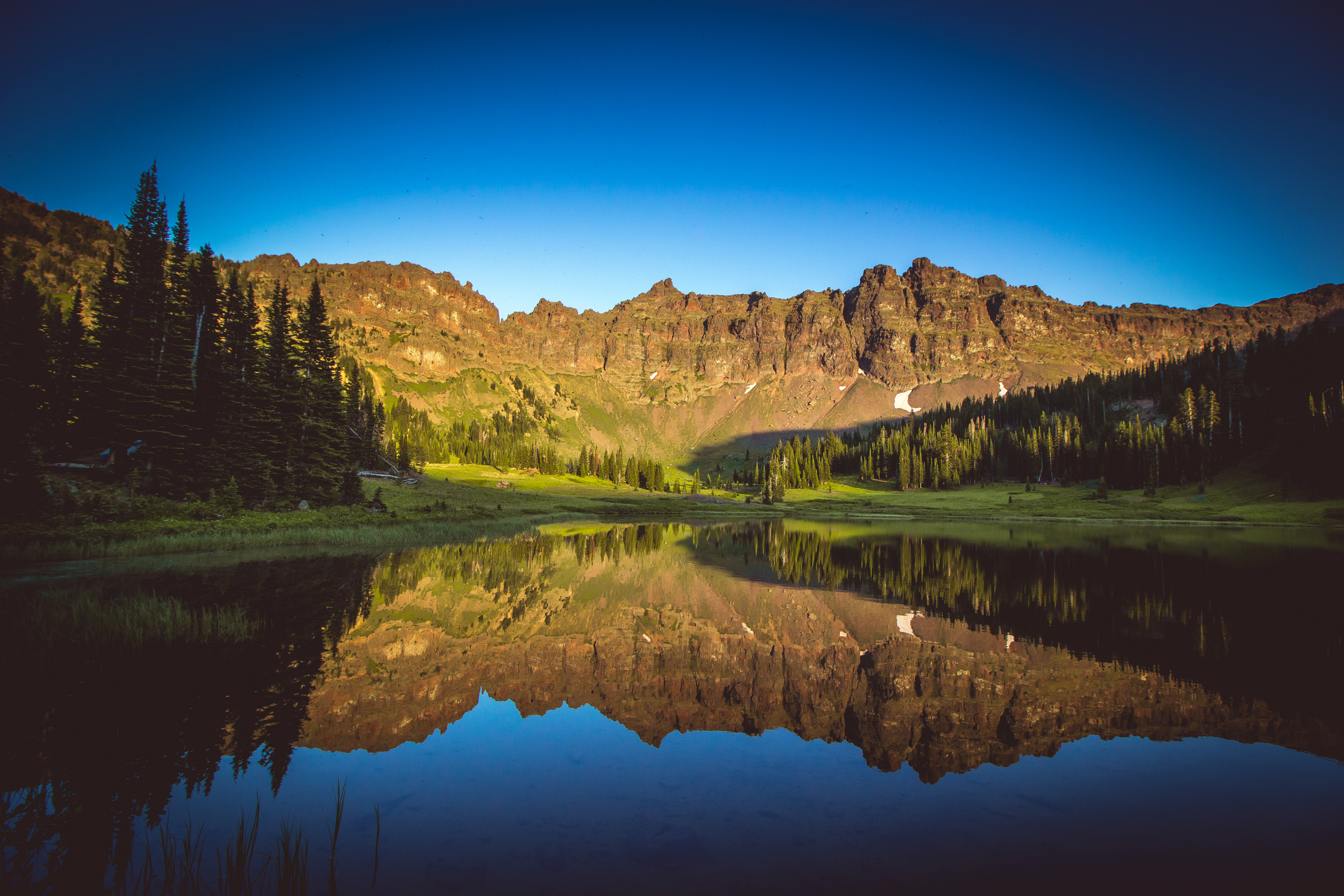 Lake reflecting rugged mountains.