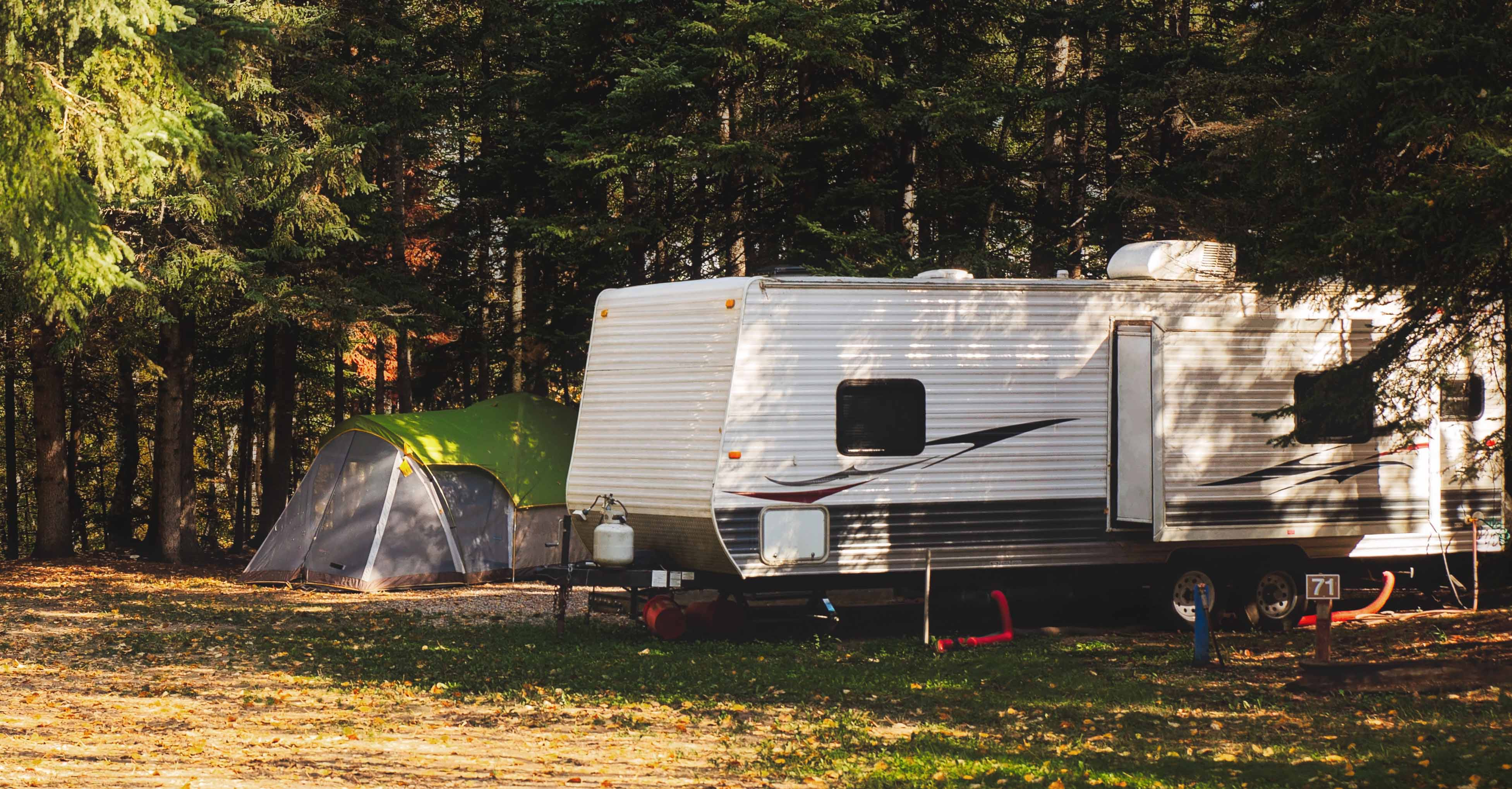 An RV in a wooded Setting.