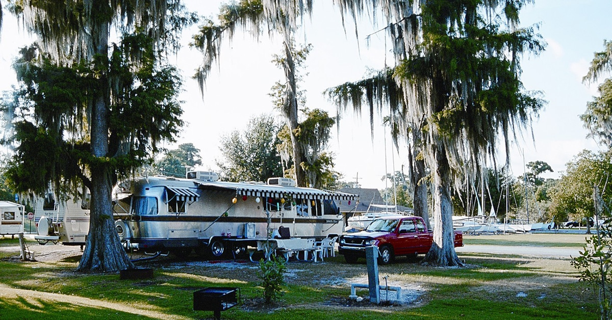 An RV near some Spanish moss trees.