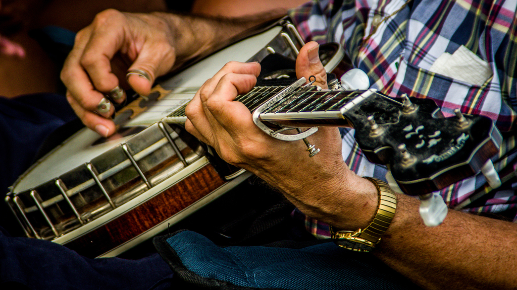 Man playing banjo close-up of chords.